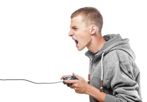 aggressiver Jugendlicher mit Gamepad in der Hand. Eltern fragen nach: Jugendlicher am Gamen - wie lange sollen Jugendliche höchstens gamen? Machen Killerspiele aggressiv etc.