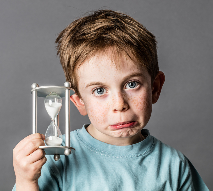 Wie lange maximal gamen? Ein Junge mit Sanduhr schaut enttäuscht